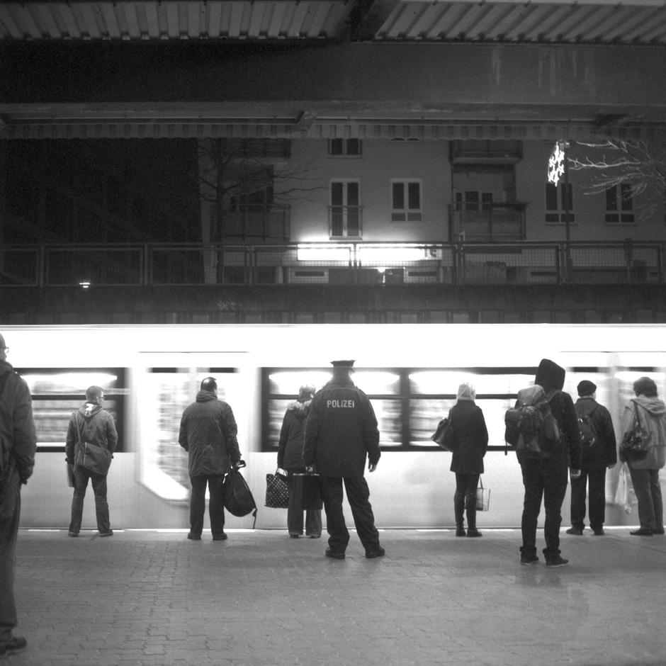 At the station of Berlin Hellersdorf (Germany) a satellite town far out in the east of the city commuters are waiting for their train to come to a halt.
